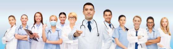 Grupo de doctores con el tablero que señalan en usted imagen de archivo