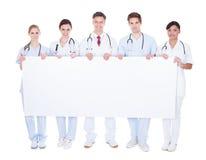 Grupo de doctores con la cartelera en blanco Imagen de archivo