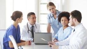 Grupo de doctores con la reunión del ordenador portátil en el hospital almacen de video