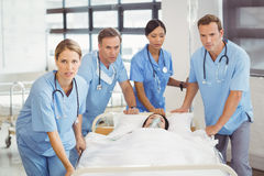 Grupo de doctores que llevan al paciente de la mujer Foto de archivo