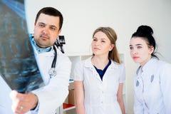 Grupo de doctores que miran la radiografía foto de archivo