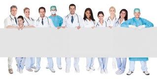 Grupo de doctores que presentan la bandera vacía Fotos de archivo libres de regalías