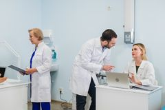 Grupo de doctores que trabajan junto en un ordenador portátil en una oficina moderna imagen de archivo