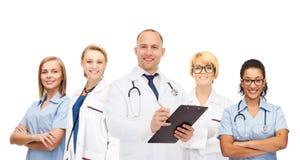 Grupo de doctores sonrientes con el tablero Fotos de archivo