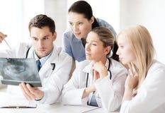 Grupo de doutores que olham o raio X Imagem de Stock