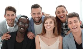 Grupo de ejecutivos jovenes que sonríen en la cámara durante un meetin del trabajo foto de archivo libre de regalías