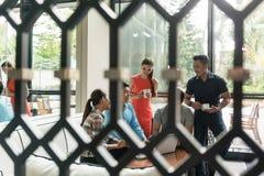 Grupo de empleados alegres que beben el café en el área del salón imagenes de archivo