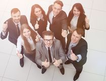 Grupo de empregados bem sucedidos que mostram os polegares acima Fotografia de Stock