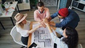 Grupo de empregados que discutem o projeto de design que junta-se então às mãos junto video estoque
