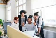 Grupo de empresários alegres novos que usam o portátil no escritório, conceito da partida foto de stock royalty free