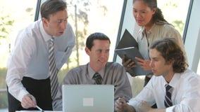 Grupo de empresários com o portátil que tem a reunião video estoque