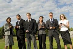 Grupo de empresários novos com telefones Fotografia de Stock Royalty Free