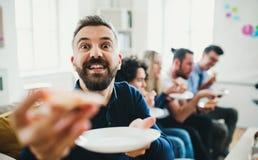 Grupo de empresários novos que têm o almoço em um escritório moderno imagem de stock