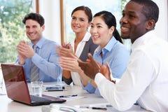Grupo de empresários que encontram-se em torno da tabela da sala de reuniões fotos de stock royalty free
