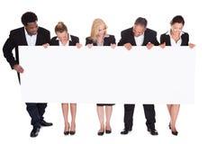 Grupo de empresários que guardam o cartaz imagem de stock