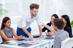Grupo de empresários que olham o homem de negócios Blaming His Colleague na reunião fotos de stock royalty free