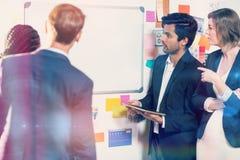 Grupo de empresários que olham o whiteboard Foto de Stock Royalty Free