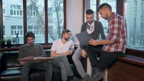 Grupo de empresários que trabalham e que tomam notas junto em um escritório pequeno Reunião do Freelancer, homem com bebida do po Fotos de Stock