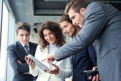 Grupo de empresários que usam uma tabuleta digital junto na frente das janelas do escritório foto de stock royalty free