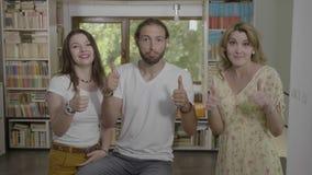 Grupo de empresarios acertados jovenes que muestran los pulgares para arriba junto - almacen de metraje de vídeo