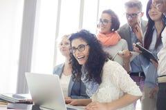 Grupo de empresarios alegres con el ordenador portátil en el escritorio en oficina creativa Imágenes de archivo libres de regalías