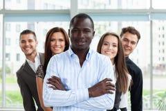 Grupo de empresarios amistosos con el líder de sexo masculino en frente imagen de archivo