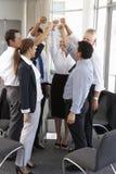 Grupo de empresarios con los brazos aumentados en el seminario de la compañía Fotografía de archivo libre de regalías
