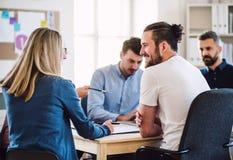 Grupo de empresarios jovenes que se sientan alrededor de la tabla en una oficina moderna, teniendo reunión fotos de archivo libres de regalías