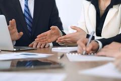 Grupo de empresarios o de abogados que discuten los papeles del contrato y figuras financieras mientras que se sienta en la tabla imagenes de archivo