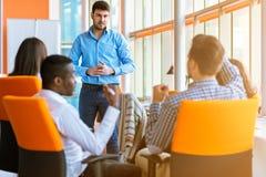 Grupo de empresarios ocasional vestidos que discuten ideas en la oficina imagen de archivo
