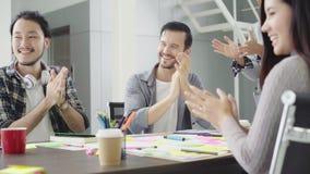 Grupo de empresarios ocasional vestidos que discuten ideas en la oficina metrajes
