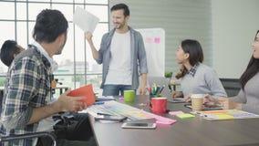 Grupo de empresarios ocasional vestidos que discuten ideas en la oficina almacen de metraje de vídeo