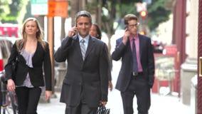 Grupo de empresarios que caminan a lo largo de la calle almacen de metraje de vídeo