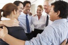 Grupo de empresarios que enlazan en círculo en el seminario de la compañía Foto de archivo libre de regalías