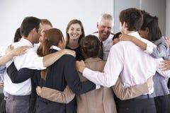 Grupo de empresarios que enlazan en círculo en el seminario de la compañía Imagen de archivo libre de regalías