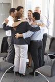 Grupo de empresarios que enlazan en círculo en el seminario de la compañía fotos de archivo