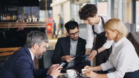 Grupo de empresarios que pagan almuerzo en café usando smartphone moderno almacen de metraje de vídeo