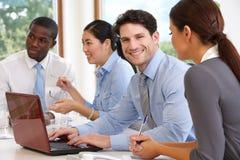 Grupo de empresarios que se encuentran alrededor de la tabla de la sala de reunión imagen de archivo