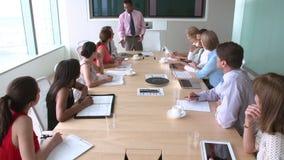Grupo de empresarios que se encuentran alrededor de la tabla de la sala de reunión almacen de metraje de vídeo