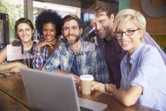 Grupo de empresarios que trabajan en el ordenador portátil en cafetería Imagen de archivo libre de regalías