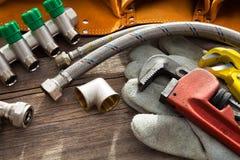 Grupo de encanamento e de ferramentas na tabela de madeira imagem de stock royalty free