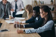 grupo de encargados que se sientan con los vasos de agua en sala de conferencias fotos de archivo