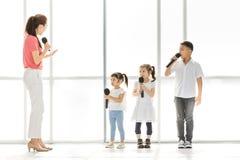Grupo de ensino do professor de crianças a cantar imagens de stock