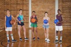Grupo de equipo de la High School secundaria que lleva a cabo un baloncesto en la corte Fotografía de archivo libre de regalías