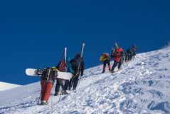 Grupo de escaladores con los esquís y los snowboards Foto de archivo libre de regalías