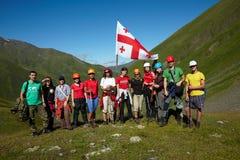Grupo de escaladores en el valle verde de la montaña con la bandera de Georgia Imagen de archivo libre de regalías