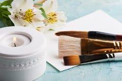 Grupo de escovas com vela iluminada, papel, fowers Imagens de Stock Royalty Free