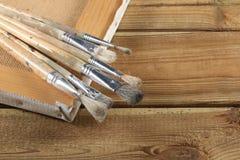 Grupo de escovas de pintura usadas com uma lona na tabela de madeira imagens de stock