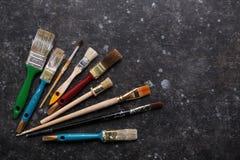 Grupo de escovas velho da pintura na obscuridade - fundo cinzento do grunge fotos de stock
