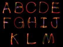 Grupo de escrita da palavra da luz no fundo preto imagens de stock